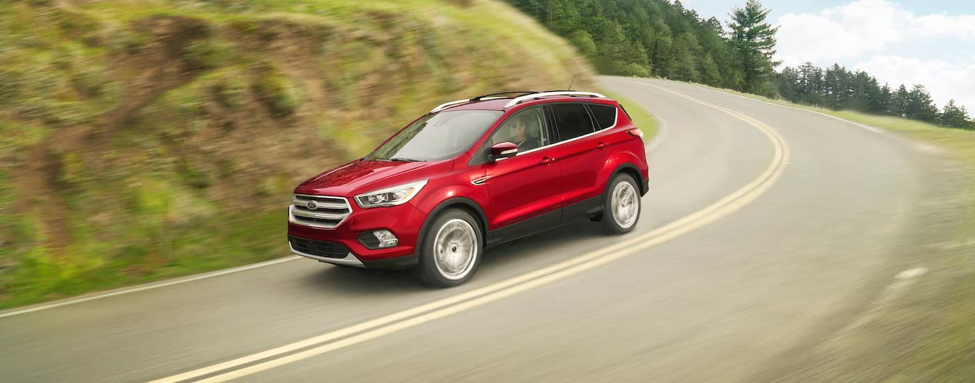 A red 2018 Ford Escape is driving down hill around a corner.