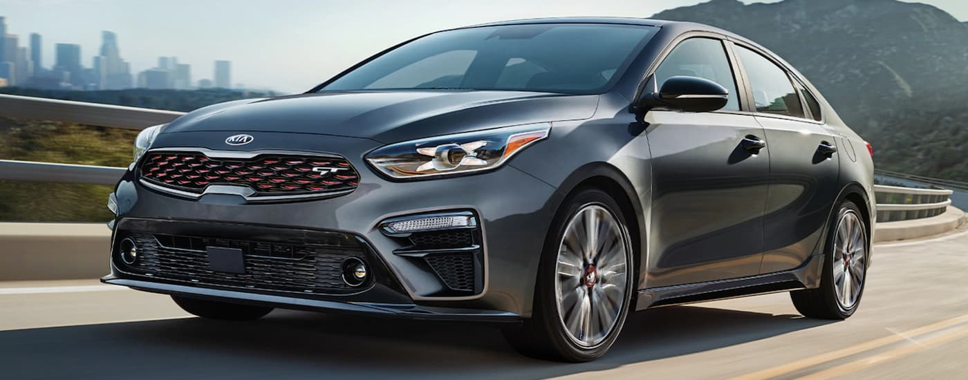 A grey 2020 Kia Forte is driving past a hill with a city in the distance.