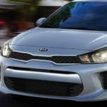 A silver 2020 Kia Rio is driving on a blurred city street near Freehold, NJ.