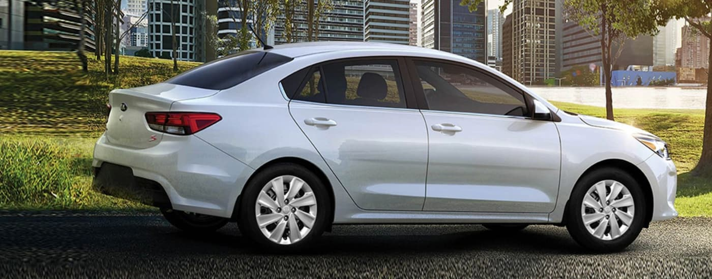 A 2020 Kia Rio, one of the smallest Kia car models, is in front of a city park.
