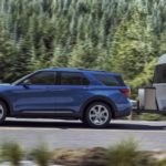 A blue 2020 Ford Explorer, one of the best Ford SUVs in Cincinnati, OH, is towing an Airstream past pine trees.