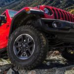 A red 2021 Jeep Wrangler Unlimited is climbing over rocks.