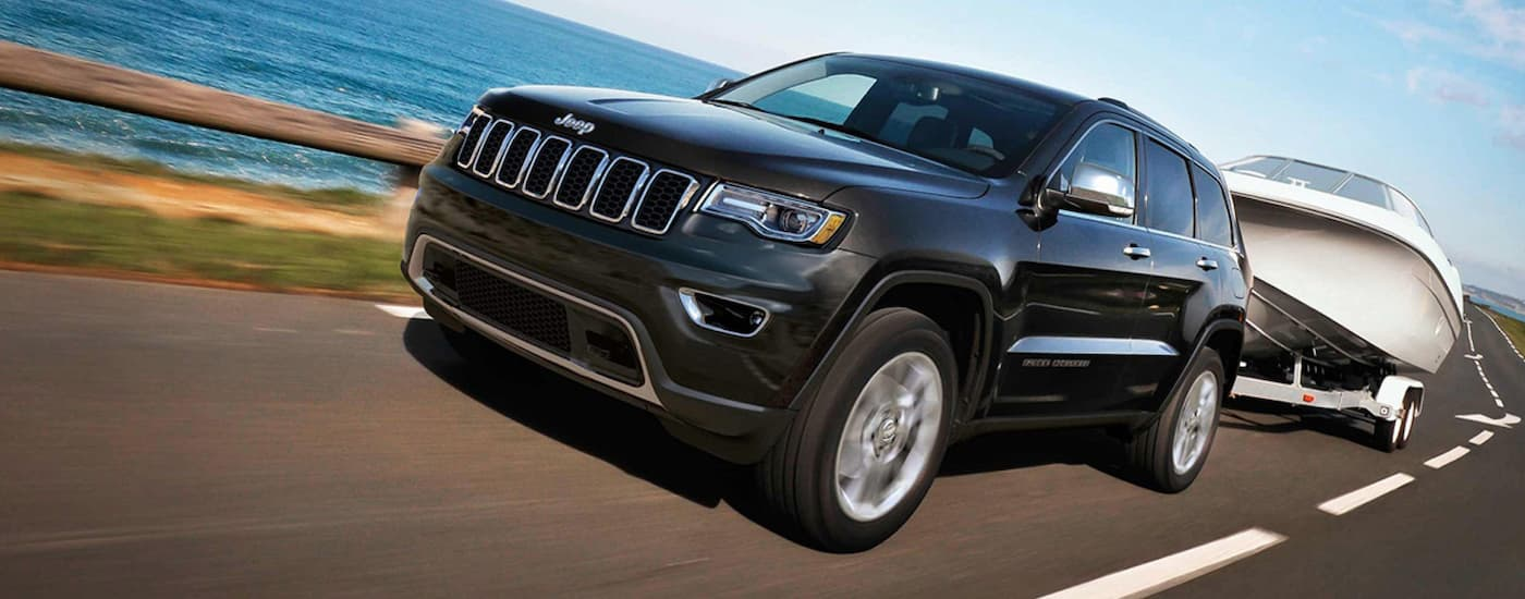 A black 2019 Jeep Grand Cherokee is towing a boat past the ocean near Costa Mesa, CA, and can be found at a used car dealer.