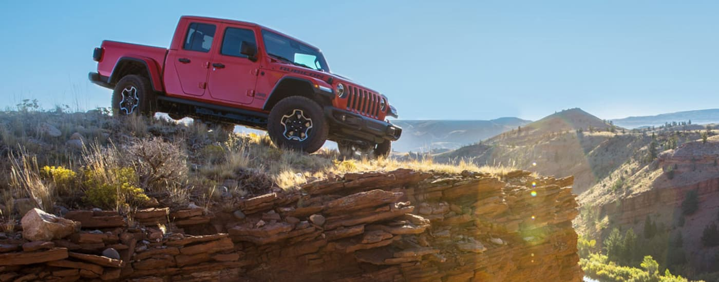A red 2020 Jeep Gladiator is parked on a cliff ledge while off-roading.