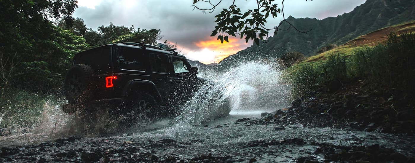 A black 2020 Jeep Wrangler is crossing a river on a trail at dusk.