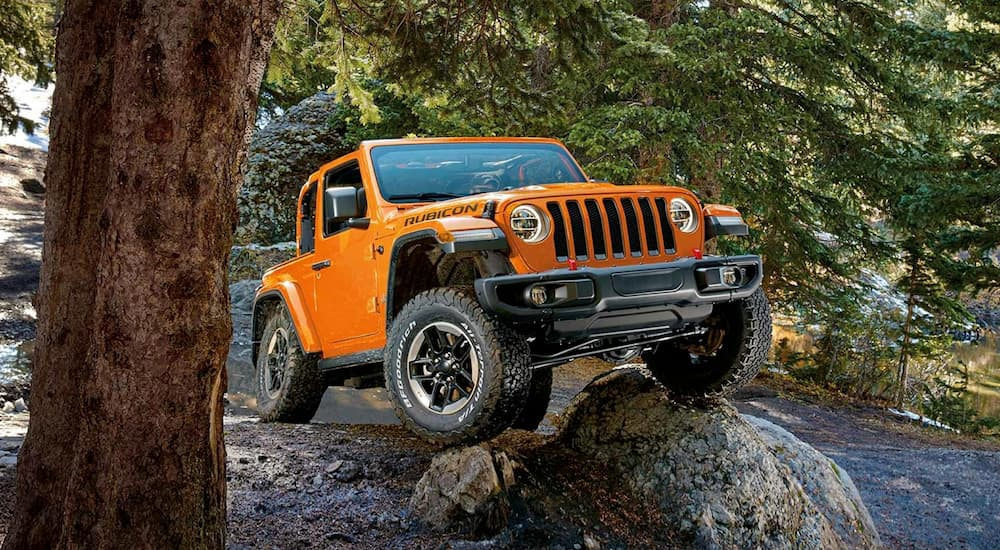 An orange 2018 Jeep Wrangler, which is popular among used cars near me in Costa Mesa, CA, is parked off-road on a rock.