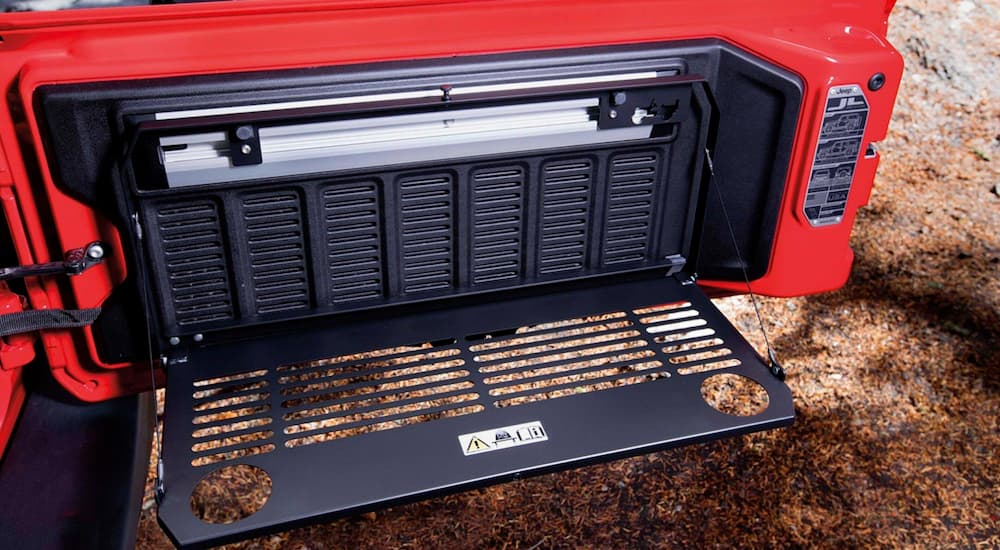 A drop down Trail Rail table is shown on a red 2020 Jeep Wrangler.