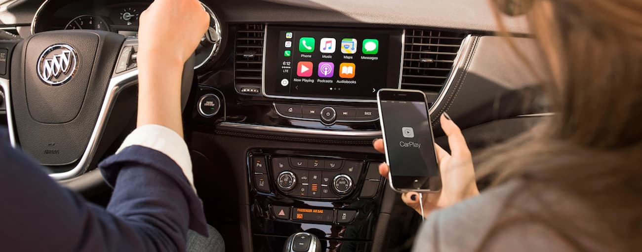 A woman is holding her phone with CarPlay on the screen while a man drives her through Atlanta, GA in their 2019 Buick Encore. Check out entertainment when comparing the 2019 Buick Encore vs 2019 Hyundai Kona.
