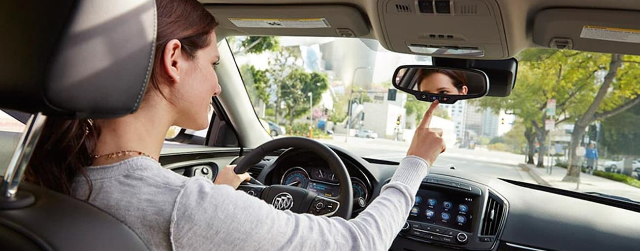A woman is pushing the OnStar button inside her 2019 Buick Encore while driving through Atlanta, GA. Check out safety when comparing the 2019 Buick Encore vs 2019 Mazda CX-3.
