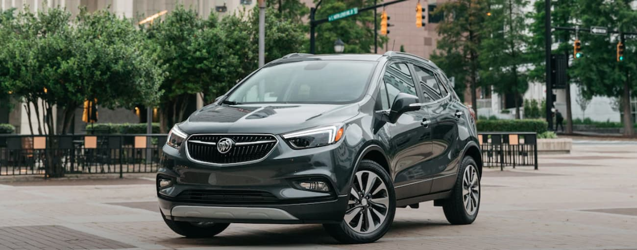 A dark colored 2019 Buick Encore is parked in a city park near Atlanta, GA. Check out performance when comparing 2019 Buick Encore vs 2019 Mazda CX-3.