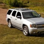 A silver 2014 Chevy Tahoe, which is popular among used SUVs for sale, is parked off-road.