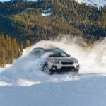 A silver used Subaru for sale, a 2019 Outback, is driving in the snow in front of a mountain.