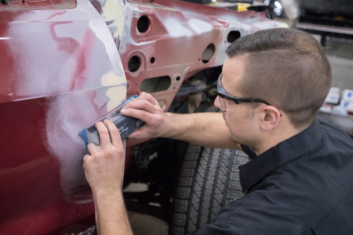 A closeup shot of a service technician's hand sanding paint