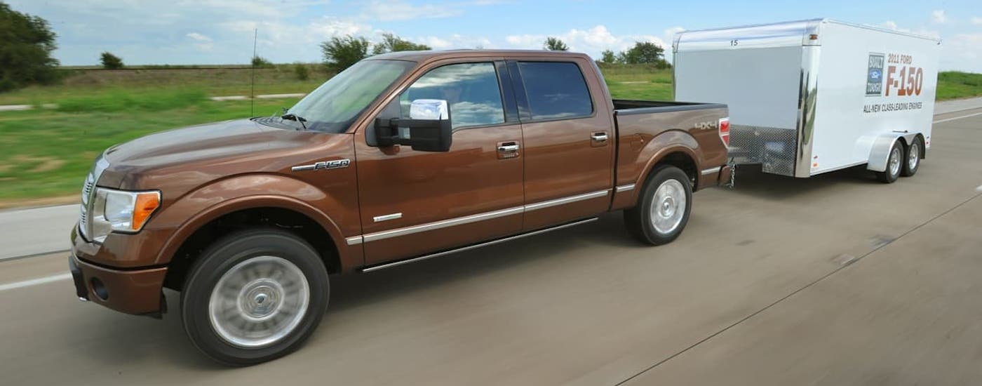 A brown 2011 used Ford F-150 is towing a trailer on a highway near Colorado Springs, CO.