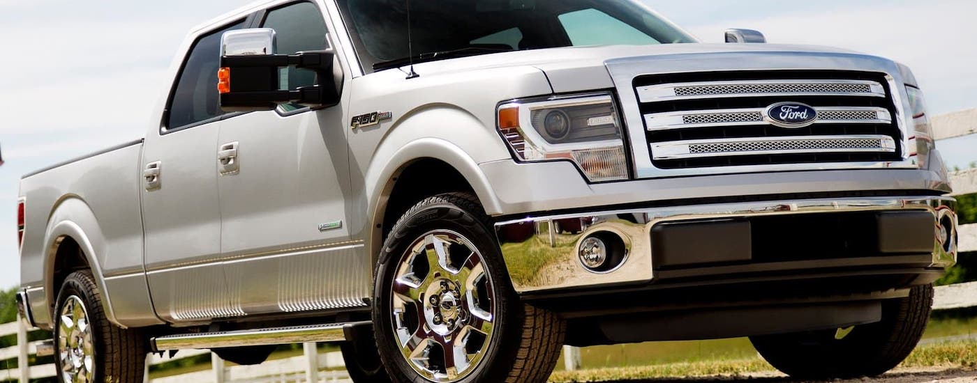 A silver 2013 Ford F-150 is parked on a dirt road in front of a white fence.