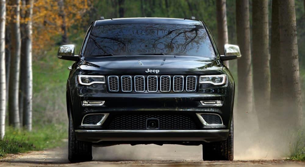 A black 2019 Jeep Grand Cherokee on a test drive from a local Colorado Springs Jeep dealership is driving a dusty road.