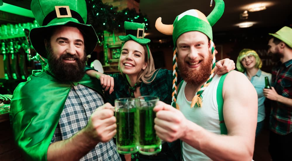 Three friends are enjoying green beer while at a St. Patrick's Day parade party near Colorado Springs, CO.