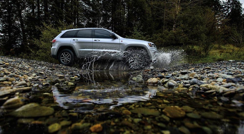 A silver 2020 Jeep Cherokee Trailhawk is shown driving through a shallow river.