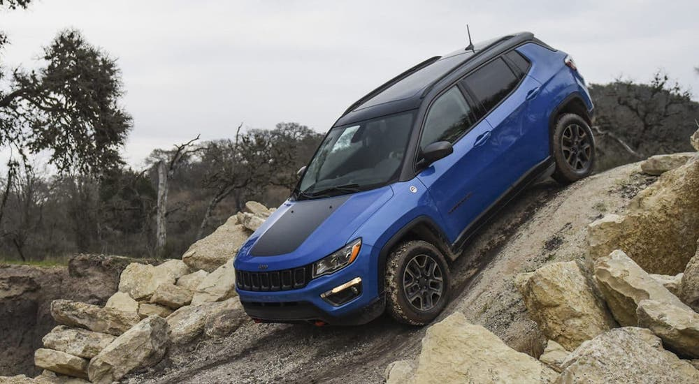 A blue 2020 Jeep Compass Trailhawk from a Jeep dealership near you is driving down a rocky hill near Colorado Springs, CO.