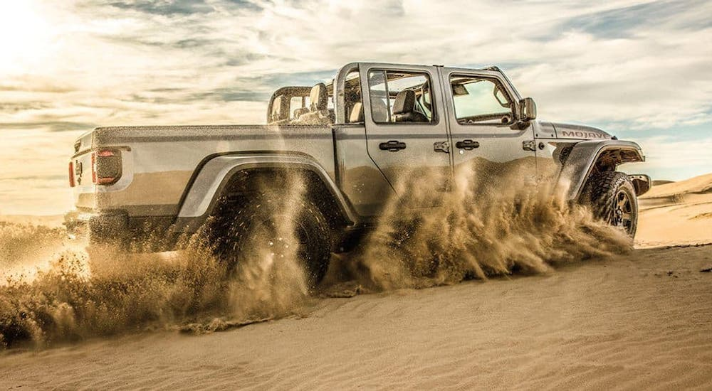 A silver 2020 Jeep Gladiator Mojave with no roof is kicking up sand.