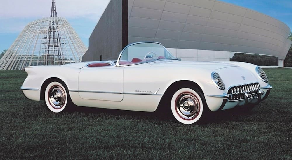 A white 1953 used Chevy Corvette is parked in front of a grey building near Cincinnati, OH.