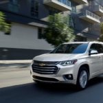 A white 2020 Chevy Traverse is driving past buildings near Cincinnati, OH.
