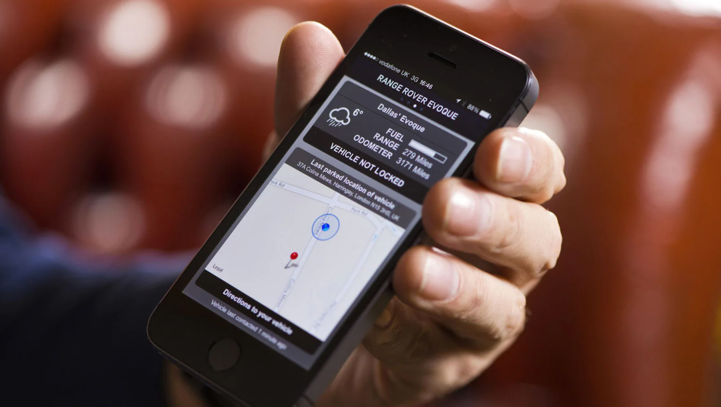 A person holding their phone using the Land Rover InControl® App.